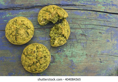 Freshly baked snack muffins with spinach on wooden surface