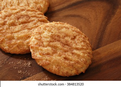 Freshly baked snickerdoodle cookies on wooden serving tray with distinctive wood grain pattern.  Closeup with shallow dof.