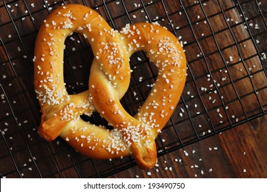 Freshly baked soft pretzel with generous sprinkling of coarse salt on wire cooling rack over rustic dark wood.  Closeup from above.