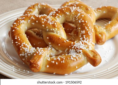 Freshly baked soft pretzels with generous sprinkling of coarse salt.  Closeup with shallow dof.