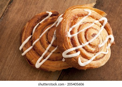 Freshly baked spiral Danish pastries with flaky puff pastry filled with apple or almond paste and drizzled with white icing for a delicious sticky sweet snack or dessert