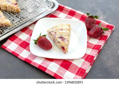 Freshly Baked Strawberry Scone on Square White Plate; More Scones in Background; Red and White Striped Napkin; Black Background