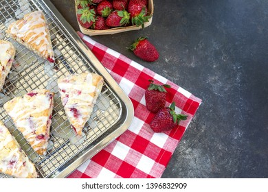 Freshly Baked Strawberry Scones on Cooling Rack with Fresh Strawberries; Red and White Checked Napkin; Black Background