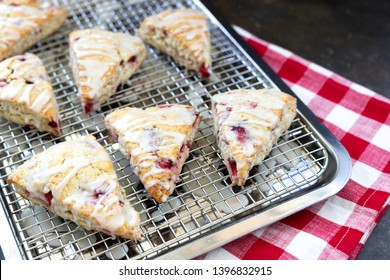Freshly Baked Strawberry Scones on Cooling Rack with Red and White Checked Napkin on Black Background