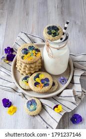 Freshly baked sugar matcha cookies with edible viola flowers