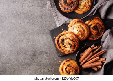 Freshly baked sweet buns on black board on grey stone background, top view