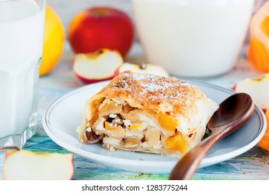 Freshly baked Tasty homemade apple strudel  on white plate placed with apples and cinnamon Served with glass milk on old worn wooden table