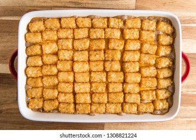 A freshly baked tater tot hot dish , shot from above on a wooden table.
