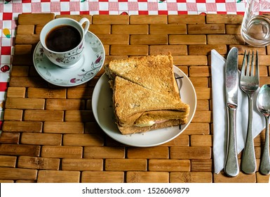 Freshly baked toast with cheese and a cup of Coffee for Breakfast. Sandwich on a plate and coffee on a table.