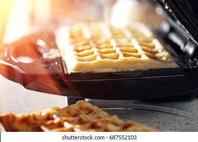 Freshly baked traditional Belgian waffles in iron waffle maker