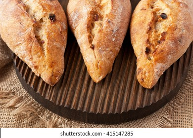 Freshly baked traditional ciabatta bread on wooden board