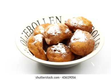 freshly baked traditional dutch oliebollen with powdered sugar in a ceramic bowl on a white background