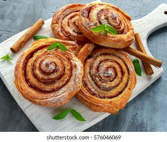 Freshly Baked Traditional Sweet Cinnamon Rolls, Swirl on white wooden board