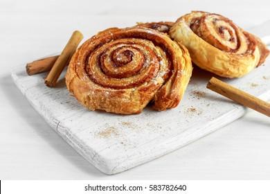 Freshly Baked Traditional Sweet Cinnamon Rolls, Swirl on white wooden board