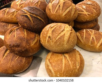 Freshly baked unsliced artisan loaves of bread piled up with streaked patterns baked into the surface