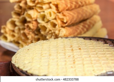 Freshly baked waffle in a waffle iron. Against the background of a stack of waffles. Shallow DOF
