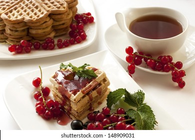 Freshly baked waffles with berries and tea cup