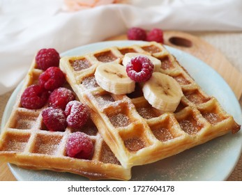 Freshly baked waffles topped with powdered sugar with raspberries and bananas