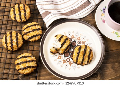 freshly baked and warm coconut macaroons with sweet chocolate on a plate