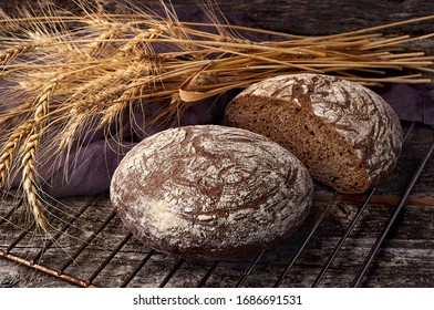 Freshly baked wheat bread, homemade cakes, still life with bread, crisp loaf of bread, still life on a rustic background, rustic style, roll, loaf.