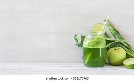 Freshly blended green smoothie in the jar on white wooden table. Template for detox recipe, copy space. Vegetarian food.