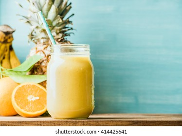 Freshly blended yellow and orange fruit smoothie in glass jar with straw. Turquoise blue background, copy space