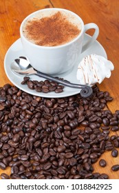 Freshly brewed cappuccino on wooden table with coffee beans