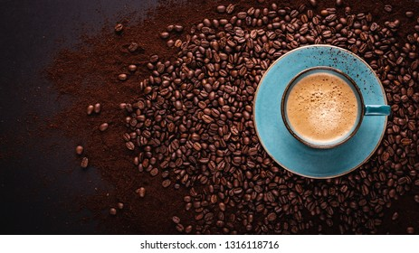 freshly brewed coffee crema in a cup on coffee beans bedded. Top view