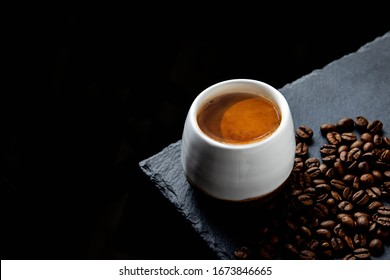 Freshly brewed espresso on a black stone table in white cup. Roasted arabica and robusta coffee beans.