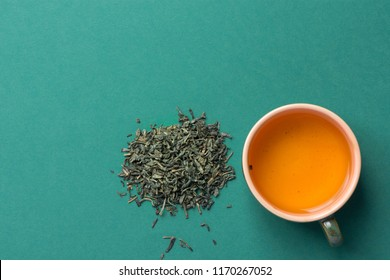 Freshly Brewed Green Tea in Ceramic Cup. Loose Leaves Scattered on Solid Dark Background. Chinese Japanese Asian Cuisine. Healthy Drinks Detox Antioxidants Concept. Minimalist Flat Lay with Copy Space