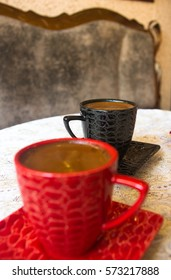 freshly brewed hot natural coffee with crema in black and red Cup