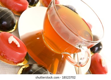 Freshly brewed red tea in a glass cup on a shiny saucer, with some colorful confectionery on a white background.