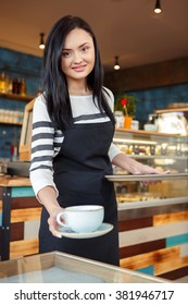 Freshly brewed! Shot of a beautiful female barista putting a cup of coffe on the table for the client smiling warmly