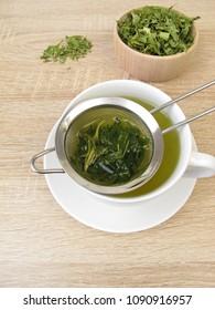 Freshly brewed tea from edible hemp in tea strainer
