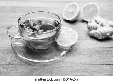 freshly brewed tea in glass cup with lemon on wooden background