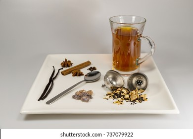 Freshly brewed tea, loose tea, a tea strainer, rock candy and spices on a square plate