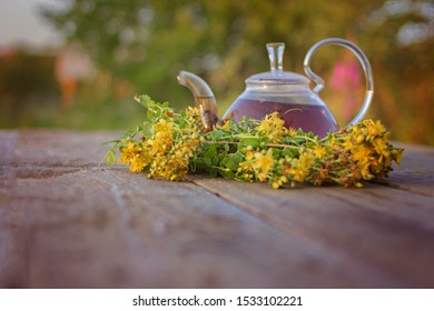 Freshly brewed tea with useful dried St. John's wort in a glass teapot on a wooden table. Selective focus