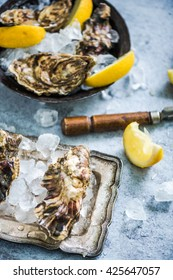 freshly catch oysters with lemon slices and ice on stone table