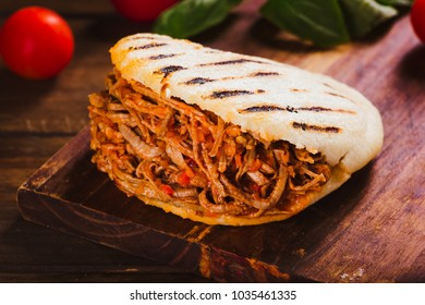 Freshly cooked Arepa with roasted meat on wood table