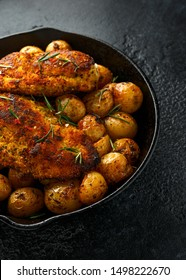 Freshly cooked breaded chicken Kiev's served with crispy baked rosemary potato in rustic cast iron skillet, pan