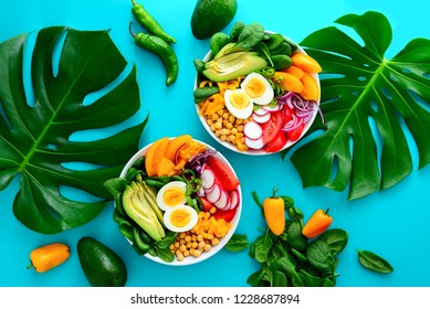 Freshly cooked Buddha bowl salad served on summer style decorated table, view from above, blank space for a text