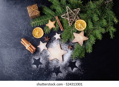 Freshly cooked Christmas star cookies over a black background with sugar powder and different christmas decration, fur tree and spices