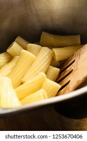 Freshly cooked and drained hot pasta (Rigatoni) in stainless steel saucepan with wooden spatula.