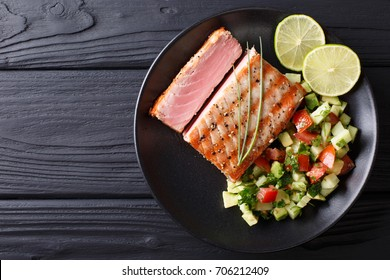 Freshly cooked grilled tuna steak with avocado cucumber salsa close-up on a plate. Top view from above horizontal