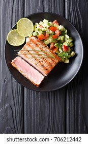 Freshly cooked grilled tuna steak with avocado cucumber salsa close-up on a plate. Top view from above vertical