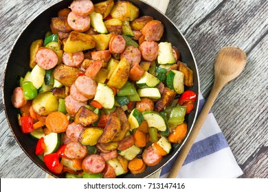 Freshly cooked one pot sausage and vegetables served in frying pan. Top view, wooden kitchen background.