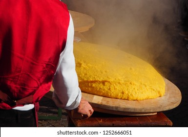 Freshly cooked polenta, still steaming  overturned on the appropriate wooden cutting board, according to the tradition of north east Italy