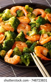 Freshly cooked prawns with broccoli close-up on a plate. vertical