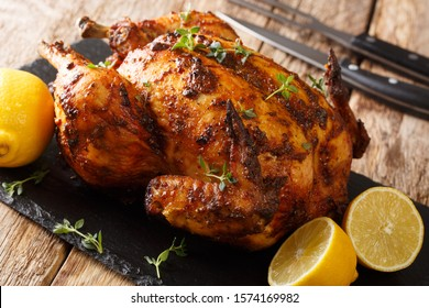 Freshly cooked rotisserie chicken with ginger and spices close-up on a slate board on the table. horizontal
