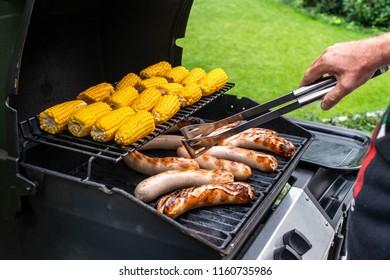 Freshly cooked sausages on a grill with corn close-up. Background of sausages made with charcoal